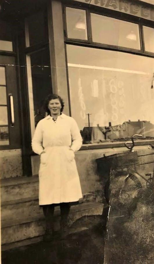 Bilde av Blid dame utenfor slakterforretning i Aagaards Plass 2